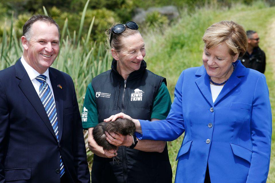 Merkel pets a native Kiwi named Whau in