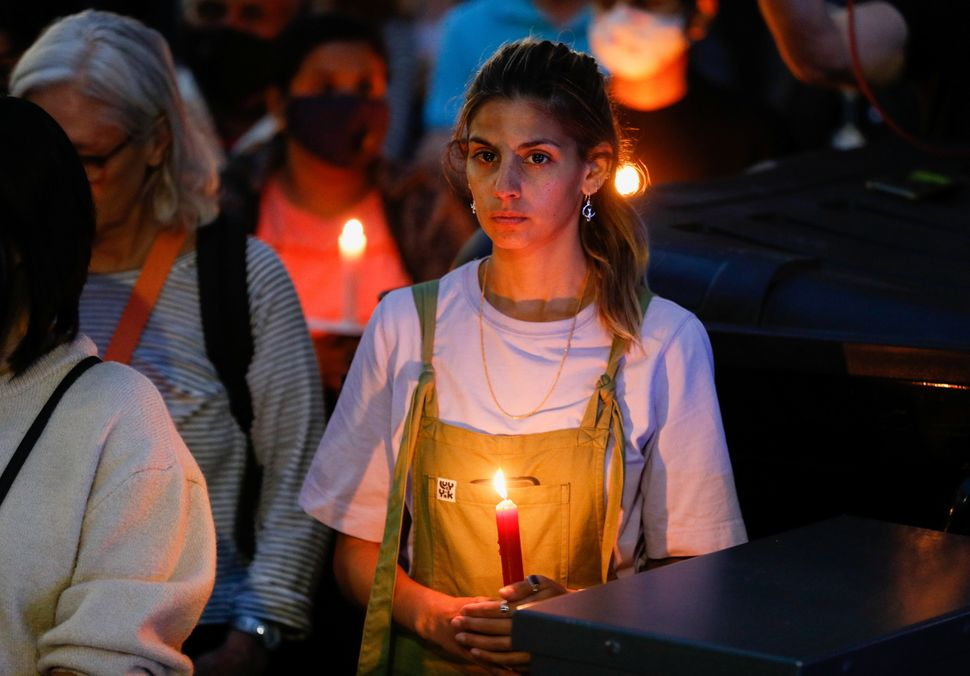 A person holds a candle during a vigil in memory of Sabina