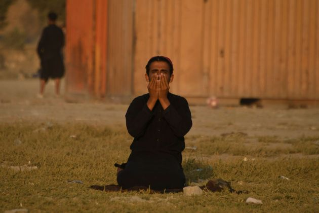 A man offers prayers at sunset at Chaman-e-Huzuri park in Kabul on September 24, 2021. (Photo by Hoshang...