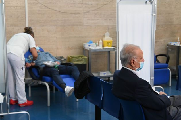 A man waits to receive the booster COVID-19 vaccine at Santo Spirito hospital in Rome, Italy, Sept. 21,...