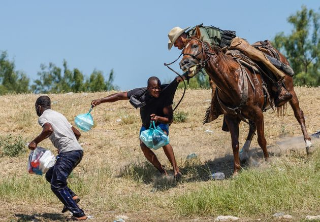 A Border Patrol agent on horseback tries to stop a Haitian migrant from entering an encampment in Del...