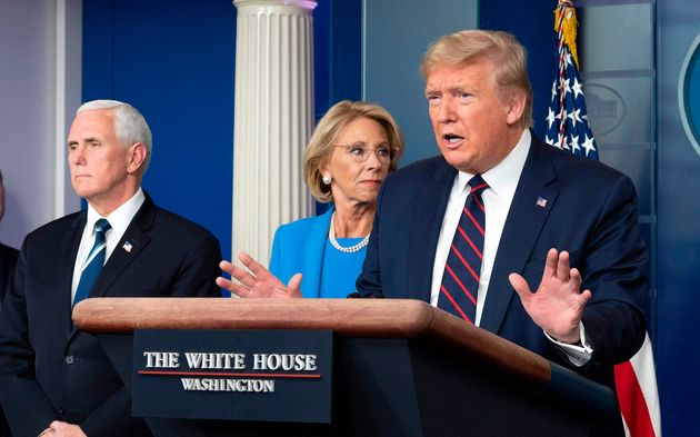 Then-Education Secretary Betsy DeVos stands with President Donald Trump and Vice President Mike Pence...