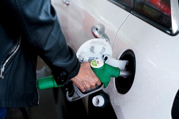 Una mujer pone gasolina a su vehículo en una