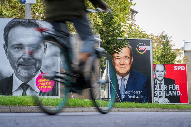 21 September 2021, Berlin: A cyclist rides past large election posters with the chancellor candidates...