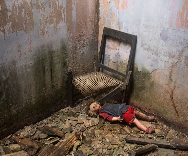 A doll next to a chair in an abandoned house.