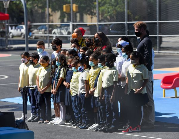 Harry and Meghan pose with schoolchildren.
