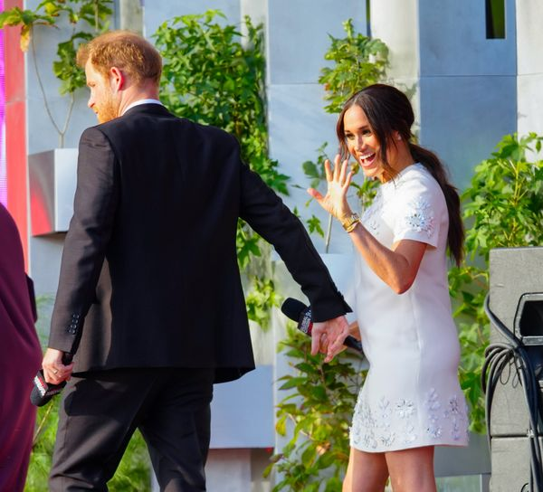 Meghan waves to concertgoers from the stage.