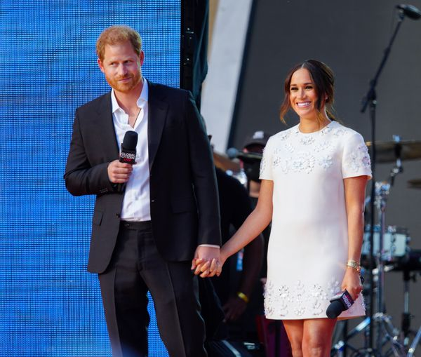 Harry and Meghan smile for the 60,000 people in attendance.