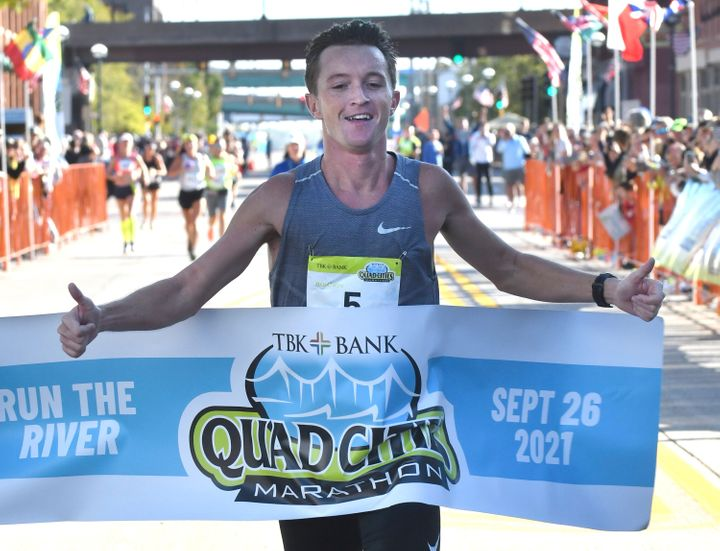 Tyler Pence of Springfield, Ill., finishes first in the TBK Bank Quad Cities Marathon on Sunday, Sept. 26, 2021, in Moline, Illinois. The two Kenyan runners who had far outpaced him were disqualified after being diverted off the course by a race volunteer bicyclist. Tyler Pence crossed the finish line in 2 hours, 15 minutes, 6 seconds to become the first U.S. runner since 2001 to win the race. (Gary L. Krambeck/Quad City Times via AP)