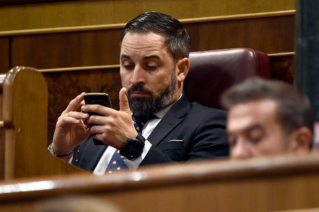 Santiago Abascal consulta su móvil en el