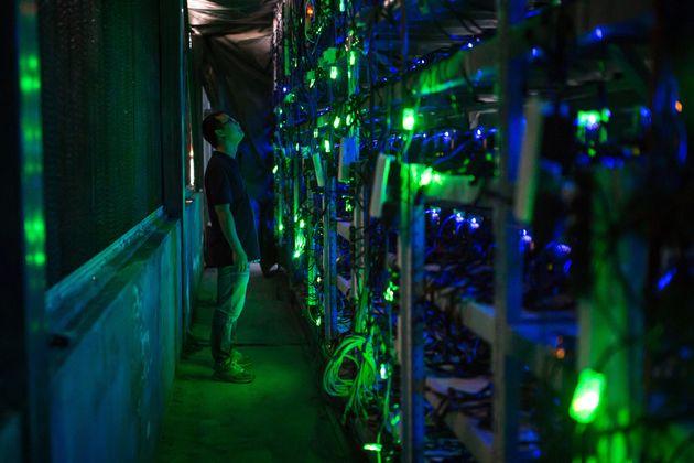KONGYUXIANG, GARZE, SICHUAN, CHINA - AUGUST 12: Haobtc's bitcoin mine site manager, Guo-hua, checks mining...