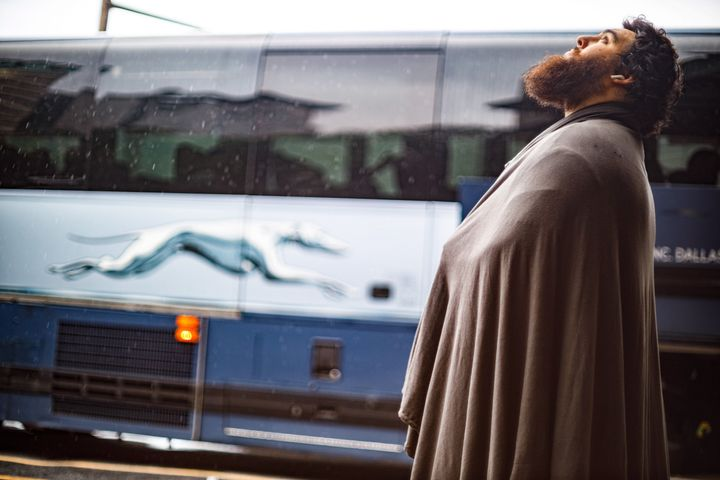 A passenger at a Greyhound bus terminal waits for a mechanic to fix a bus's flat tire on July 14, 2021.