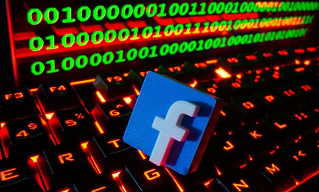 A 3D printed Facebook logo is pictured on a keyboard in front of binary code in this illustration taken...