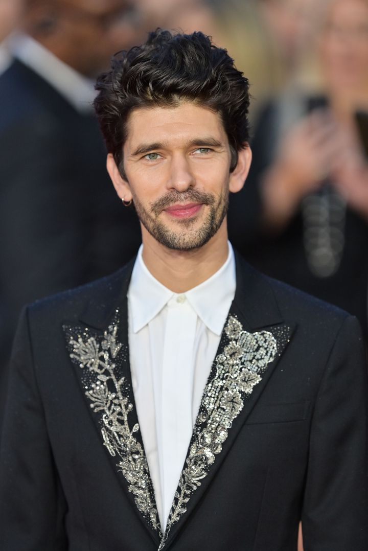 Ben Whishaw, in a jeweled jacket, smiles for the cameras.
