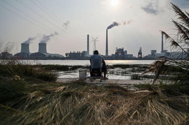 An angler is seen fishing along the Huangpu river across the Wujing Coal-Electricity Power Station in...