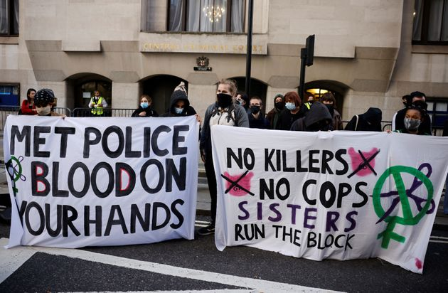 Demonstrators hold banners as they await the sentencing of British police officer Wayne Couzens for the...