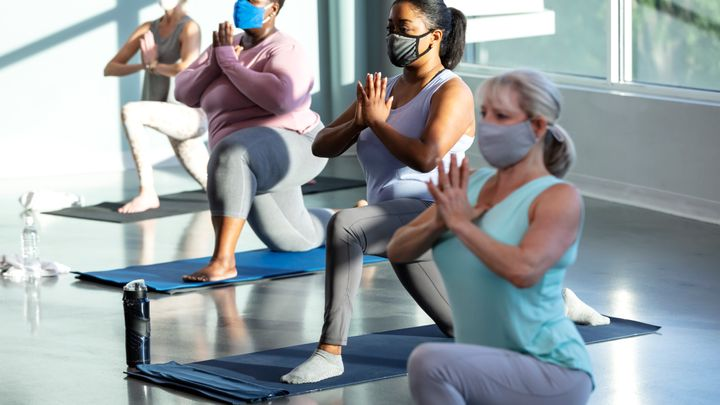 A multi-ethnic group of four women taking a yoga class, in a crescent lunge pose on knee with prayer hands. They are indoors, side by side, with the focus on the African-American woman second from right. She is in her 30s. They are wearing protective face masks, trying to prevent the spread of coronavirus during the COVID-19 pandemic.
