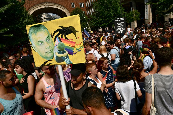 People taking part in a gay pride parade hold a banner depicting Hungarian Prime Minister Viktor Orbán in Budapest, Hu