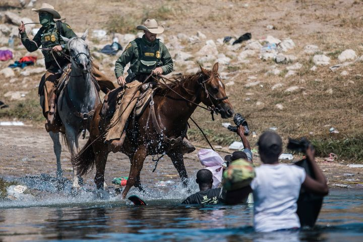 U.S. Customs and Border Protection mounted officers attempt to contain migrants as they cross the Rio Grande from Ciudad Acuñ