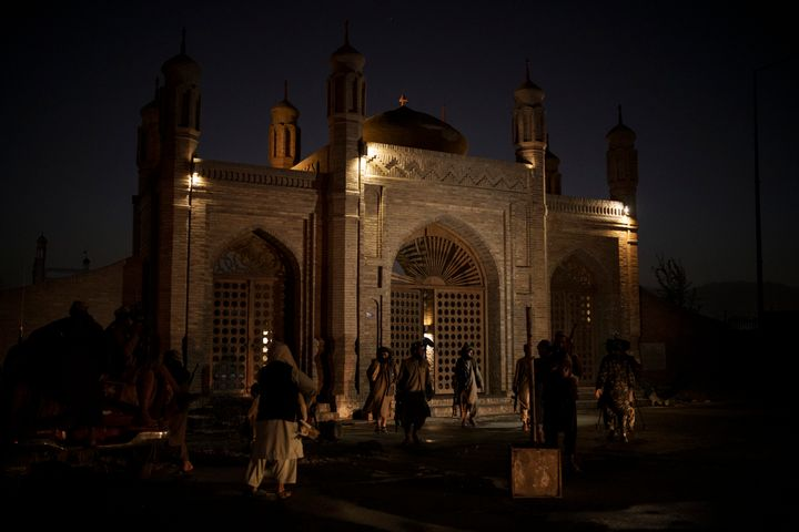 Taliban fighters walk at the entrance of the Eidgah Mosque after an explosion in Kabul, Afghanistan, Sunday, Oct. 3, 2021. A