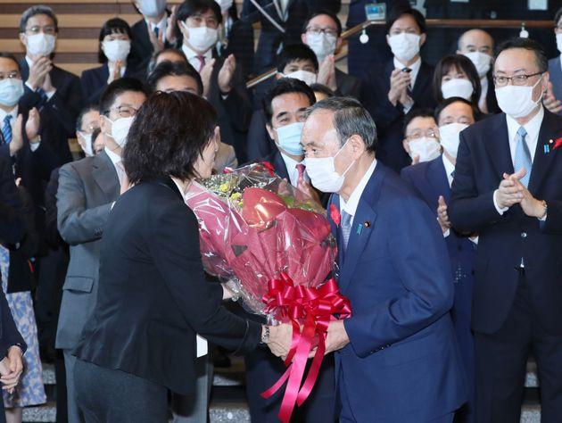 内閣を総辞職し、花束を手渡される菅義偉首相(手前右)=2021年10月4日、東京・永田町