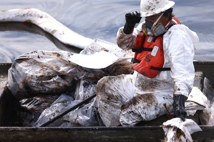 A worker in a protective suit cleans oil Monday in the Talbert Marsh wetlands after a 126,000-gallon oil spill off Huntington