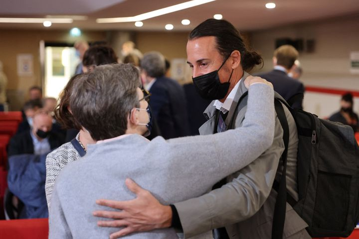 Olivier Savignac, right, one of the victims, greets an attendee during the publishing of a report by an independant commissio