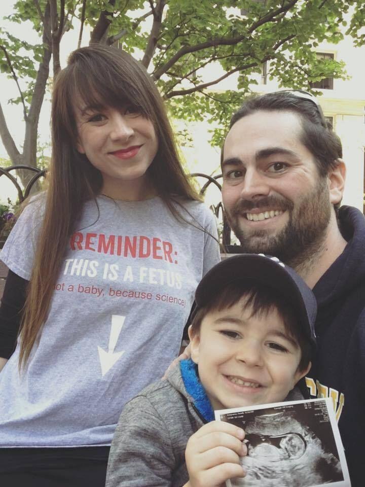 La autora con su pareja y su hijo, anunciando su embarazo.