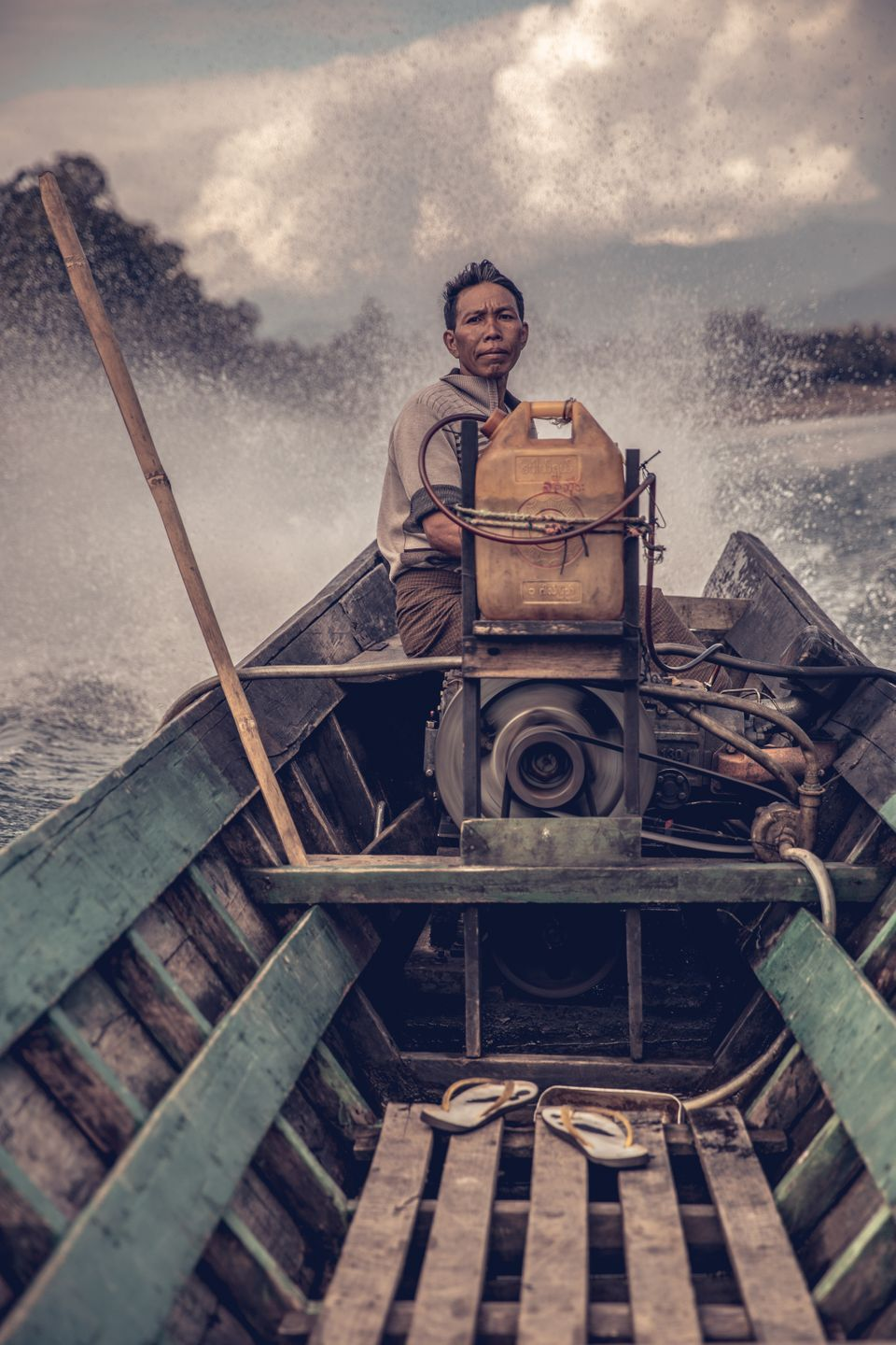 A local boatman in remote northern Myanmar, tackling a challenging water channel filled with rocks and...