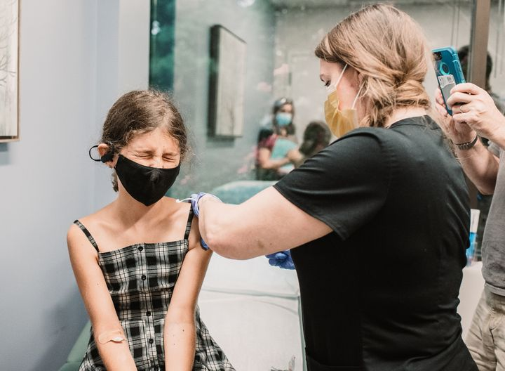 The author's 10-year-old daughter receives her first COVID-19 vaccine dose.