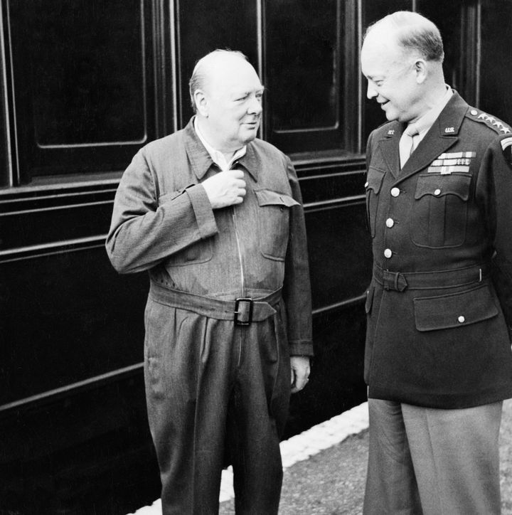 Churchill demonstrates the zipper on his famous siren suit to General Dwight D. Eisenhower during their tour of troops preparing for D Day near Lydd and Hastings in Kent in May 1944.