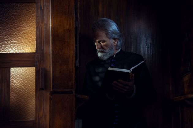Senior priest in confession booth
