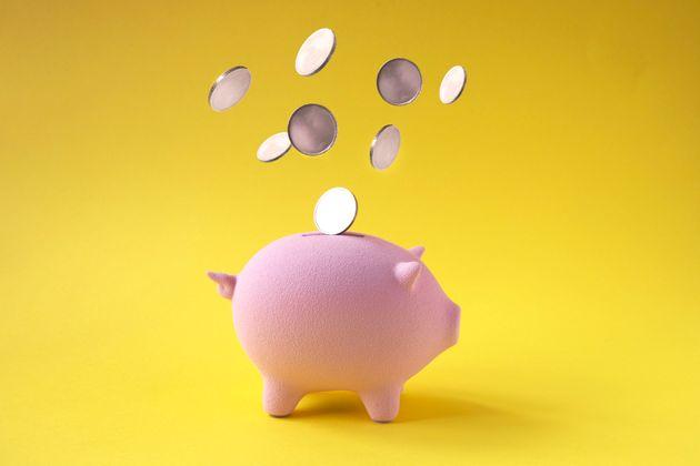 Coins falling into pink piggy bank on yellow background.
