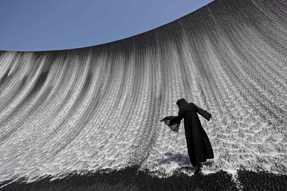 A woman walks onto the Expo Water Feature in Dubai on Oct.