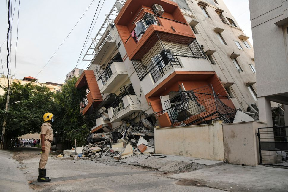 An emergency responder watches a multistory apartment building that collapsed without any reported casualties...