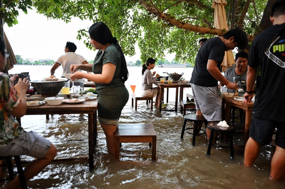 Diners stand while eating at the Chaopraya Antique Cafe as floodwaters from Thailand's Chao Phraya River...