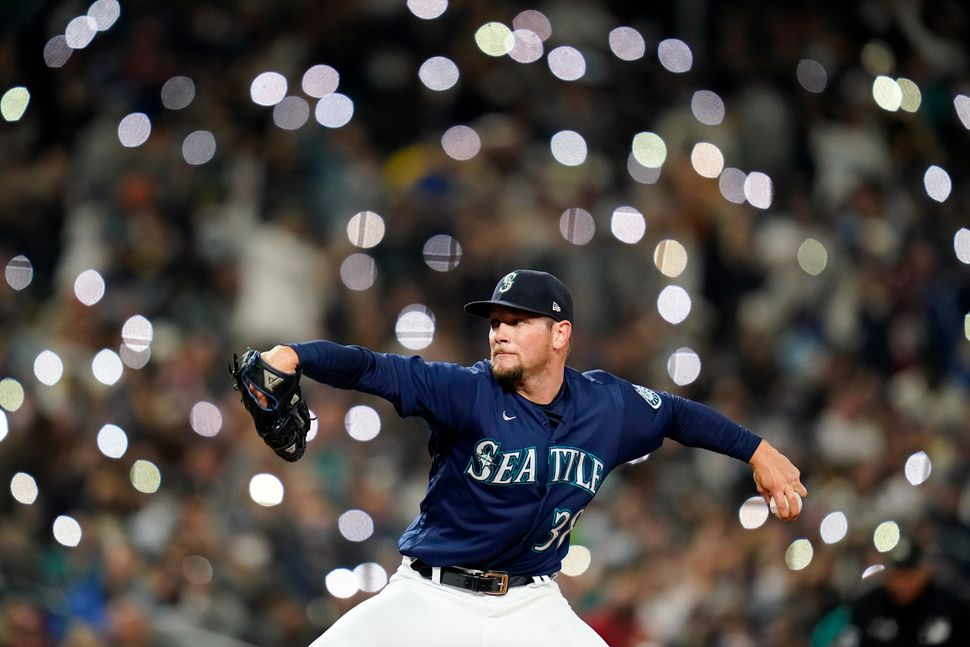 Cellphones light up in the seats behind Seattle Mariners reliever Anthony Misiewicz as he pitches against...