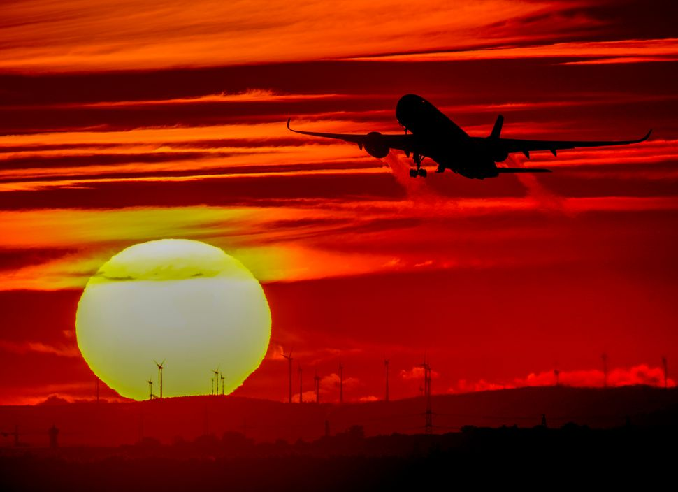 An aircraft takes off at the international airportas the sun sets in Frankfurt, Germany, on Oct.