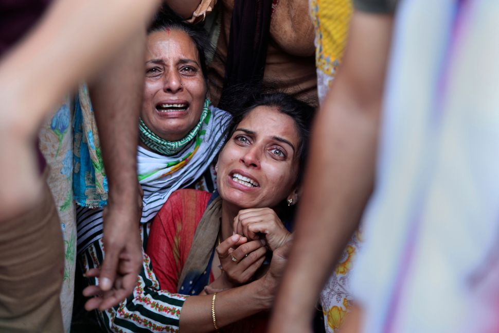 Aradhana, center, wife of Deepak Chand, a schoolteacher who was killed in Kashmir, mourns before the...