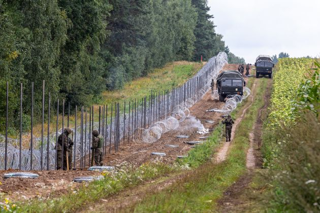 Polish Army Soldiers build a fence with concertina wire at the Belarusian border in order to stop immigrants...
