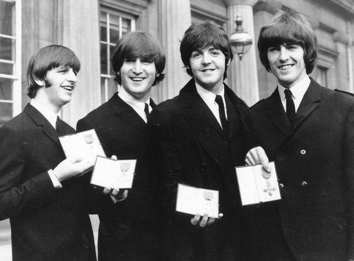 The Beatles, from left: Ringo Starr, John Lennon, Paul McCartney and George Harrison. They are seen displaying the Member of The Order of The British Empire medals presented to them by Queen Elizabeth II at Buckingham Palace in 1965.