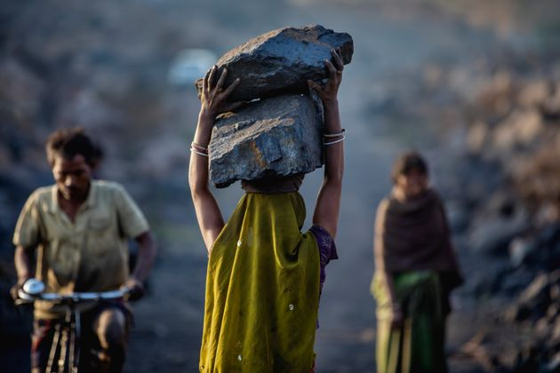 A female worker has piled coal on her head while she is working in Jharia coal field where a large amount...