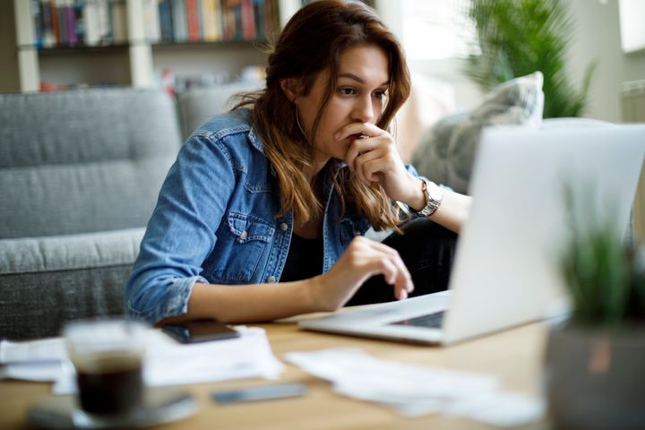 Worried young woman working at home