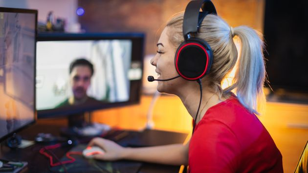 Teenage Girl Playing Multiplayer Games on Desktop Pc in his Dark