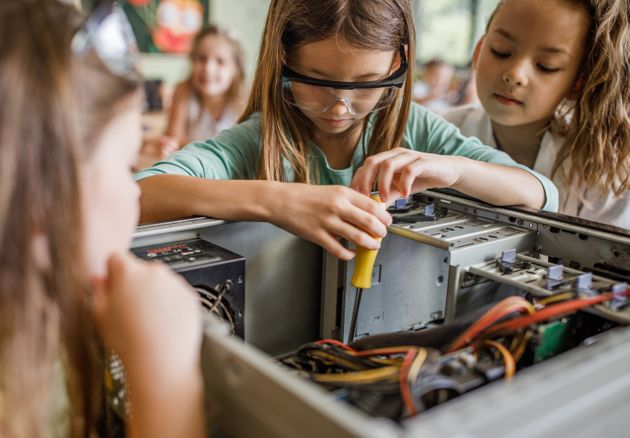 Team of school girls repairing computer during science project in the