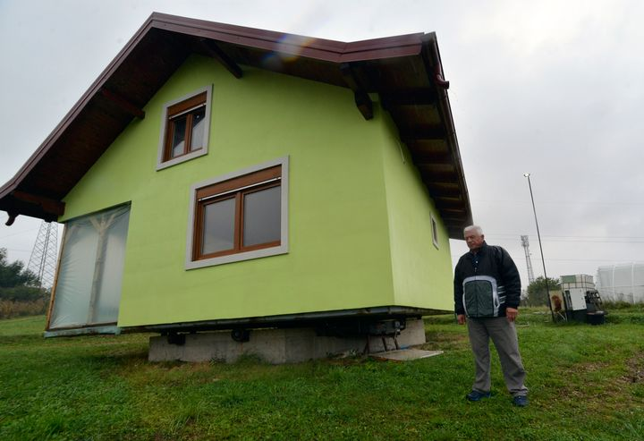 Vojin Kusic's stands in front of his rotating house in a town of Srbac, northern Bosnia, Sunday, Oct. 10, 2021. The house can rotate a full circle to satisfy his wife's shifting desires as to what she should see when she looks out of the windows of her home. (AP Photo/Radivoje Pavicic)