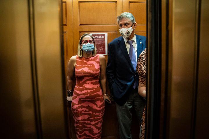 Sen. Kyrsten Sinema (D-Ariz.) and Sen. Joe Manchin (D-W.Va.) board an elevator on Capitol Hill, Sept. 30, 2021.