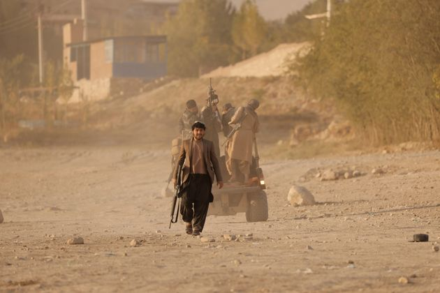 A Taliban fighter walks as he and others take a day off to visit the amusement park at Kabul's Qargha...