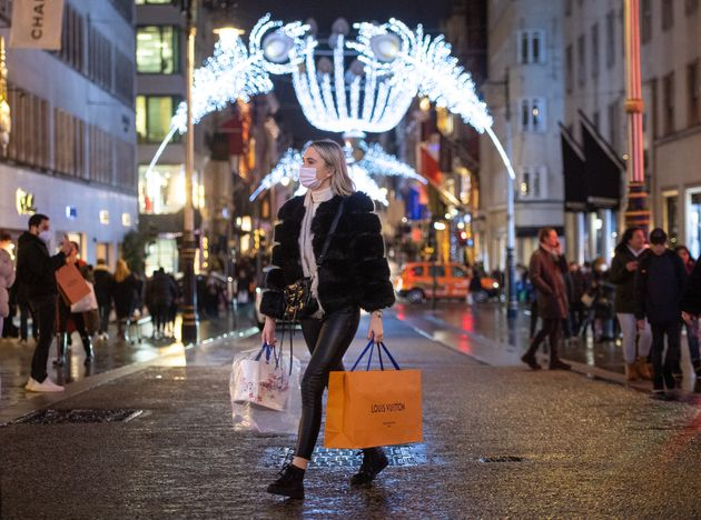 Shoppers pass Christmas light displays on New Bond Street in central London. (Photo by Dominic Lipinski/PA...