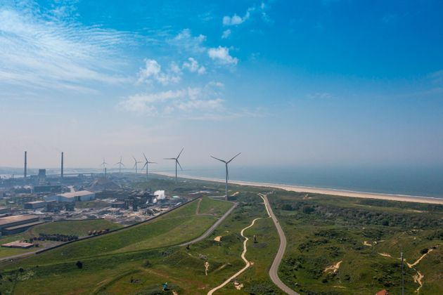 Drone shot of a steel mill in the early morning. Blast furnace and coal depot. Wind turbines near the...